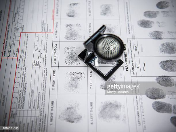 Fingerprints with loupe on arrest form in forensic laboratory