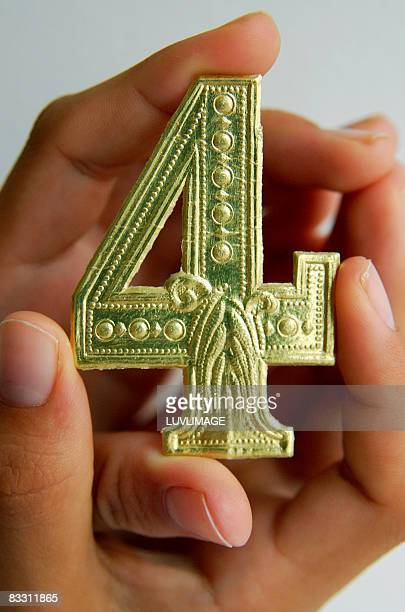 fingers holding a golden number four