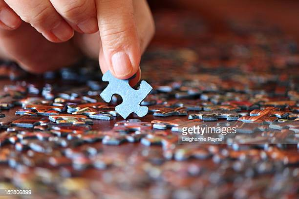 Fingers placing jigsaw puzzle pieces