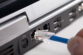 Fingers plugging usb cable into back of laptop