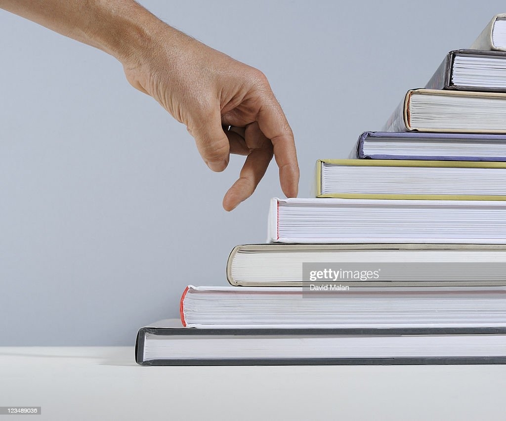 Fingers walking up a staircase of books. : Stock Photo