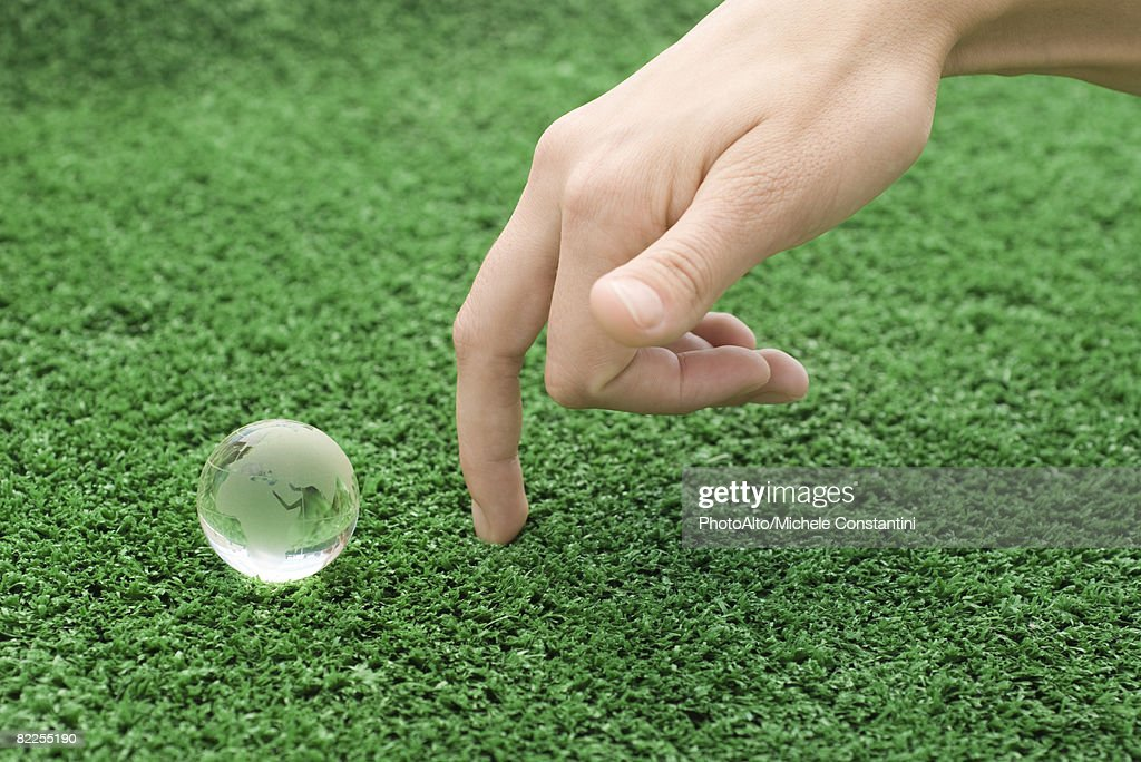 Fingers walking up toward small glass globe : Stock Photo