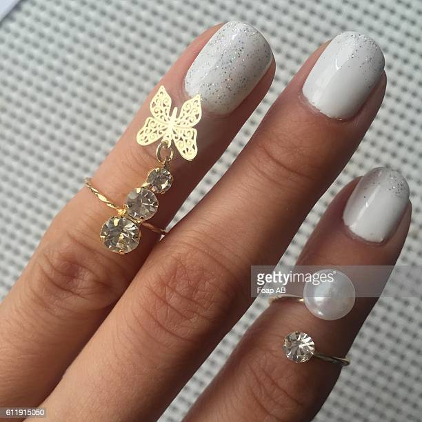 fingers with rings on it showing white nail polish on fingernail - white nail polish stock pictures, royalty-free photos & images