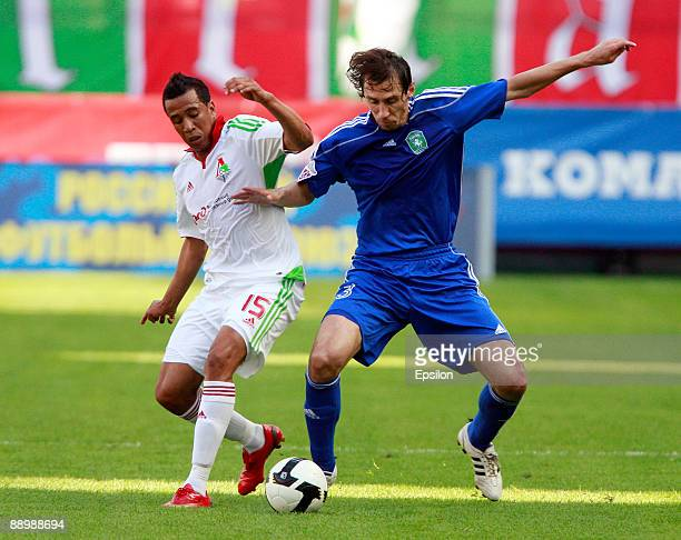 Fininho of FC Lokomotiv Moscow battles for the ball with Valeri Klimov of FC Tom Tomsk during the Russian Football League Championship match between...