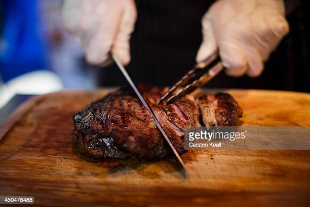 A finished grilled rib eye steak is cutted on a cutting board during a cooking demonstration at a barbecue in the courtyard of the US Embassy on...