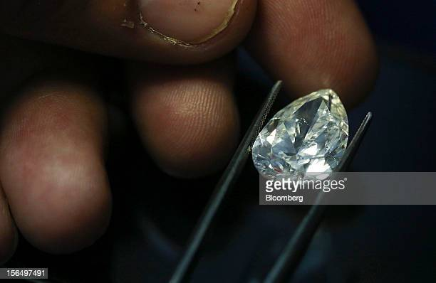 A finished pearshaped diamond is displayed by an employee using tweezers in this arranged photograph at the Shrenuj Botswana Ltd sightholder office...