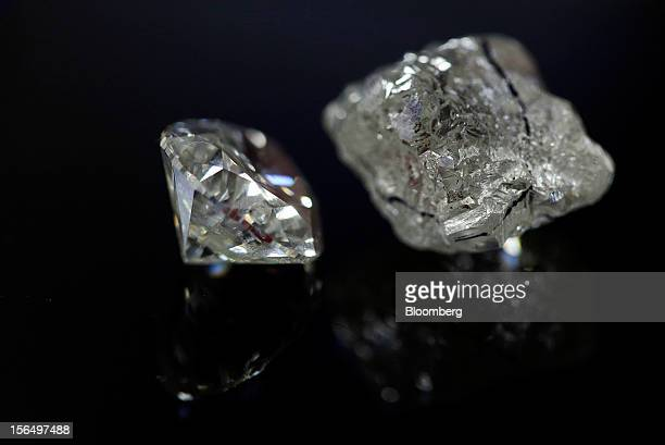 A finished roundshaped diamond left and an uncut diamond with cutting marks are displayed in this arranged photograph at the Shrenuj Botswana Ltd...