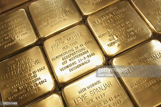 Finished Stolpersteine, which are concrete cobblestones afixed with a brass commemorative plaque, lie on a worktable at the Stolpersteine...