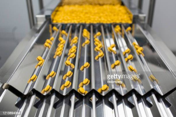 Finished tablets cascade down the channels of a packaging machine during the manufacture of the Favipiravir antiviral medicine, a joint venture...
