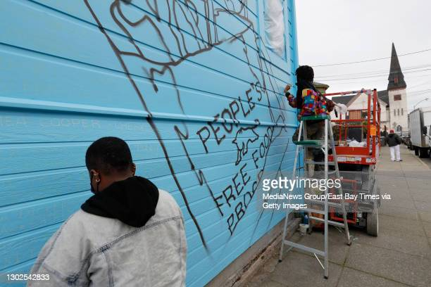 Finishing touches are put on the mural by Rachel Wolfe-Goldsmith during its unveiling on Jilchristina Vest's home at the corner of Center and 9th...