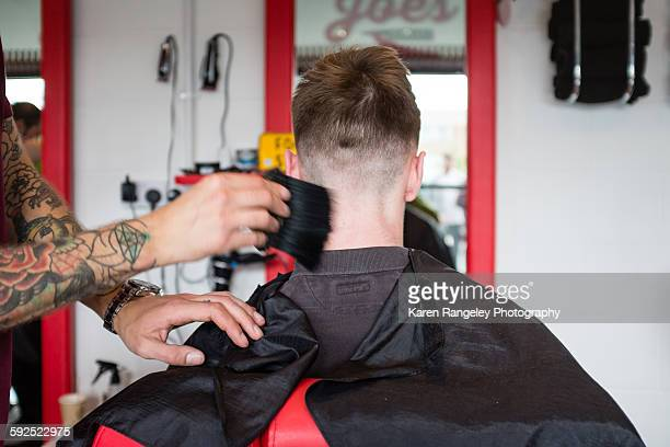 Finishing touches as barber Will brushes away the hair from his clients nape