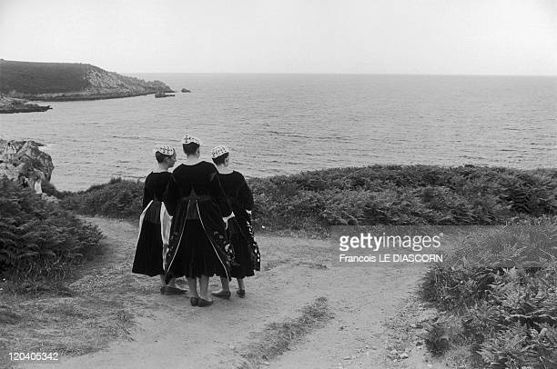 Finistere Brittany France Three young Breton girls in traditional costumes of the Baud region at the headland of BeuzecCap Sizun