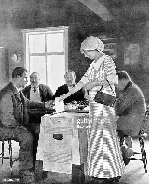 A Finnish woman voting at a Parliamentary Election Woman is standing as she puts her vote into ballot box as men sit and watch