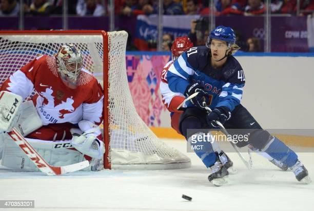 Finland forward Antti Pihlstrom passes from around the Russia goal against Russia defenseman Slava Voynov and Russia goalie Semyon Varlamov in the...