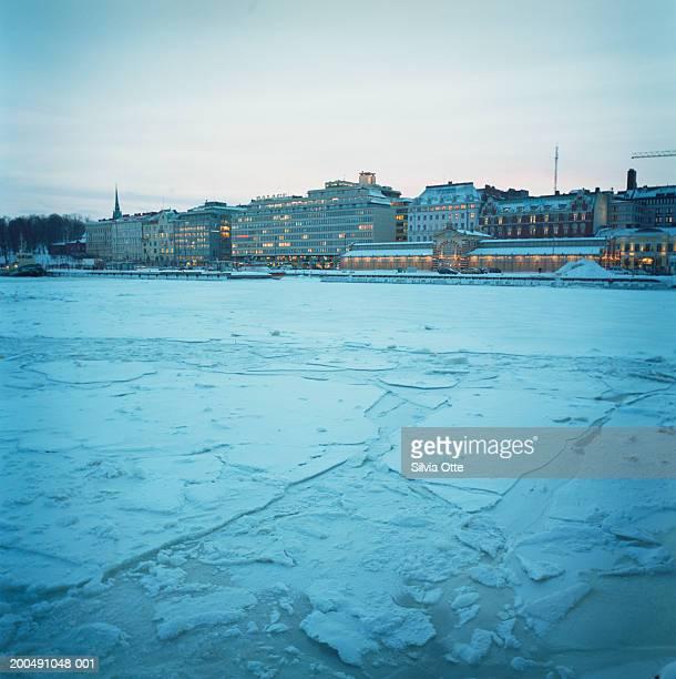 Finland, Helsinki, Etelasatama, skyline and frozen harbour at dusk