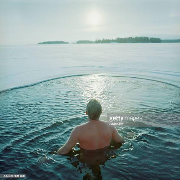 Finland, Helsinki, man ice water swimming in frozen Baltic Sea