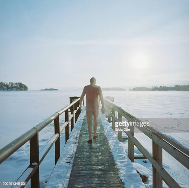 Finland, Helsinki, naked man walking along pier on frozen Baltic Sea