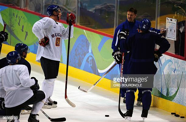 Finland ice hockey players listen to head coach Jukka Jalonen's instructions during a practice session at the Canada Hockey Place in Vancouver two...