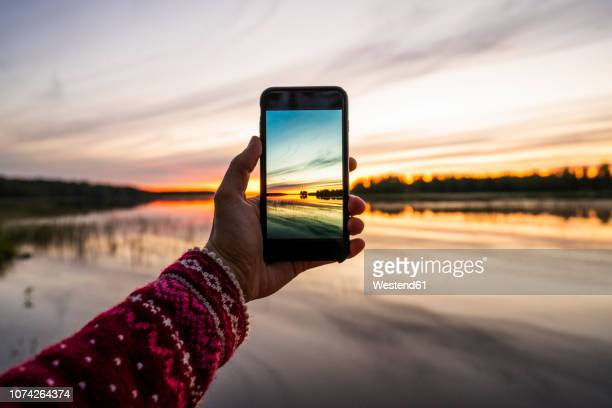 finland, kajaani, person taking a smartphone picture of the sunset - fotohandy stock-fotos und bilder