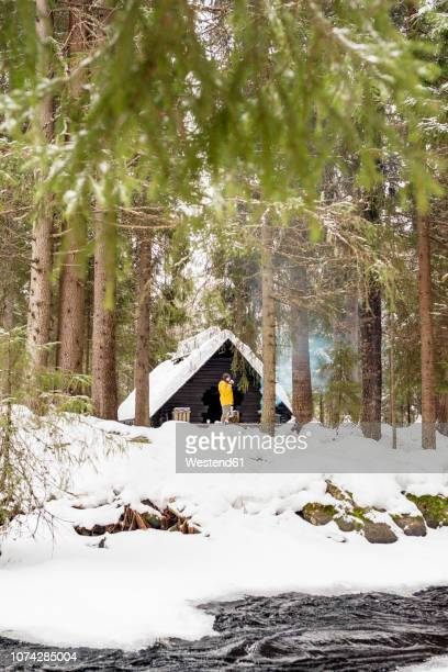 Finland, Kuopio, woman standing in front of wooden hut in winter