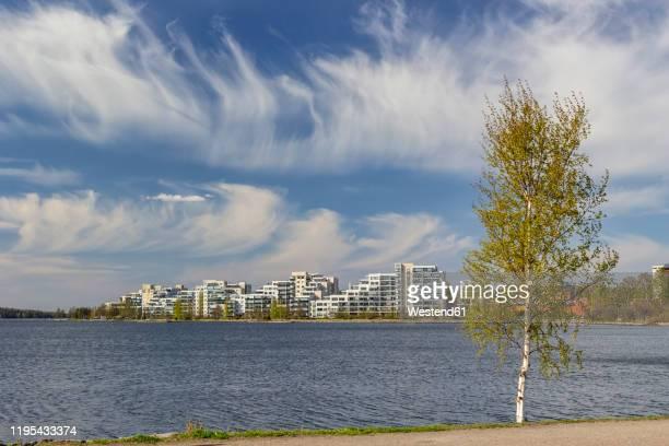 finland, lahti, clouds over vesijarvi lake and modern residential buildings in spring - lahti finland stockfoto's en -beelden