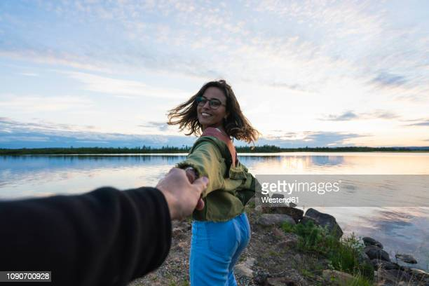 finland, lapland, happy young woman holding man's hand at the lakeside at twilight - finlandia fotografías e imágenes de stock