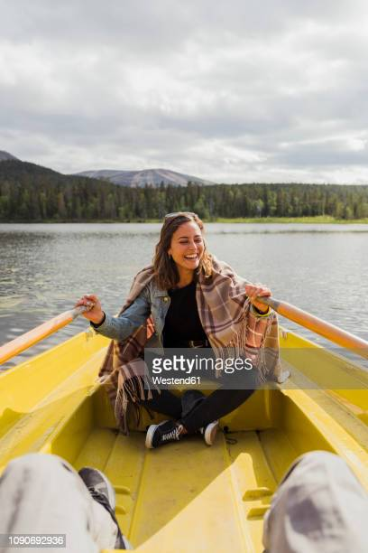 finland, lapland, laughing woman wearing a blanket in a rowing boat on a lake - finlandia fotografías e imágenes de stock