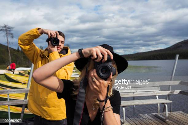 finland, lapland, man and woman taking pictures on jetty at a lake - photographer stock photos and pictures