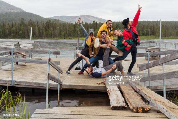Finland, Lapland, portrait of happy playful friends posing on jetty at a lake
