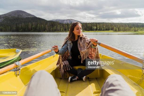 Finland, Lapland, woman wearing a blanket in a rowing boat on a lake