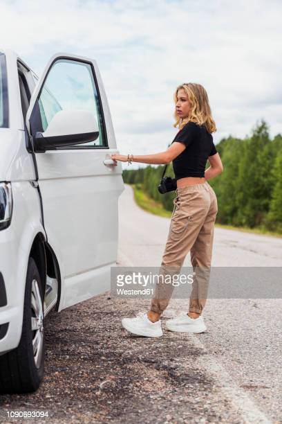 finland, lapland, young woman at country road getting into a car - eintreten stock-fotos und bilder