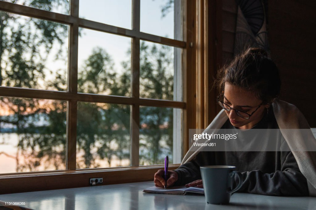 Finland, Lapland, young woman sitting at the window at a lake writing into diary : Stock Photo
