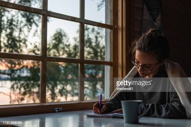 finland, lapland, young woman sitting at the window at a lake writing into diary - diary stock pictures, royalty-free photos & images