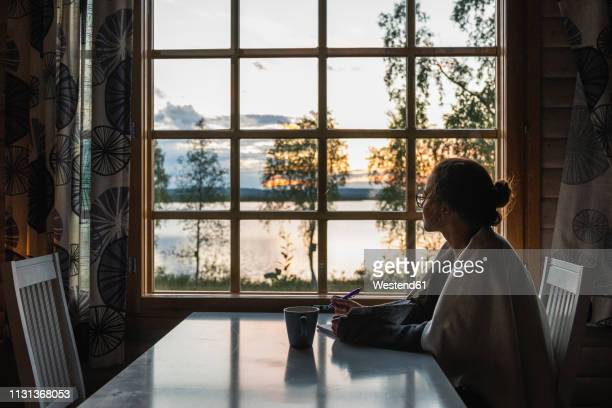 finland, lapland, young woman sitting at the window looking at a lake - authors stockfoto's en -beelden