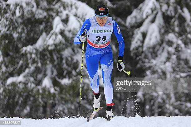 Finland's AinoKaisa Saarinen competes during the FIS Ski World Cup Ladies' 10 Km Individual Classic race on February 1 2014 in Dobbiaco Norway's...