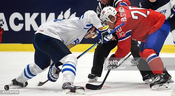 Finland's Andreas Martinsen and Norway's Janne Pesonen fight for a puck during the group B preliminary round ice hockey match Norway vs Finland of...