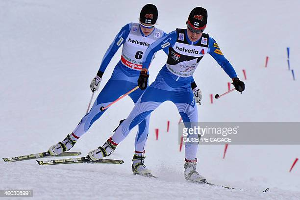 Finland's Anne Kylloenen and her compatriot Kerttu Niskanen compete in the women's 15 km freestyle pursuit at the Nordic Skiing World Cup in Toblach...