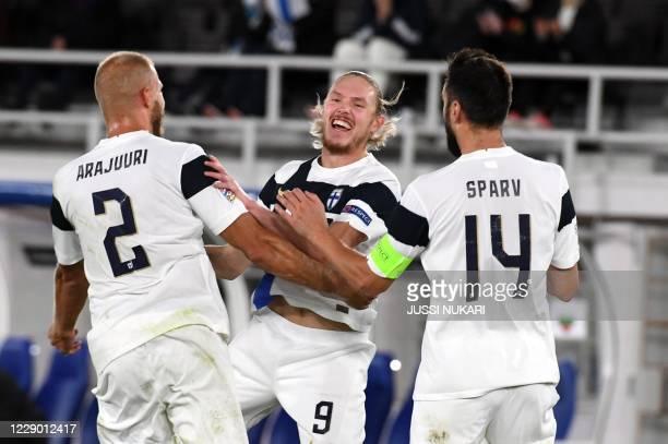 Finland's defender Paulus Arajuuri, goalscorer Finland's midfielder Fredrik Jensen and Finland's midfielder Tim Sparv celebrate scoring 2:0 during...