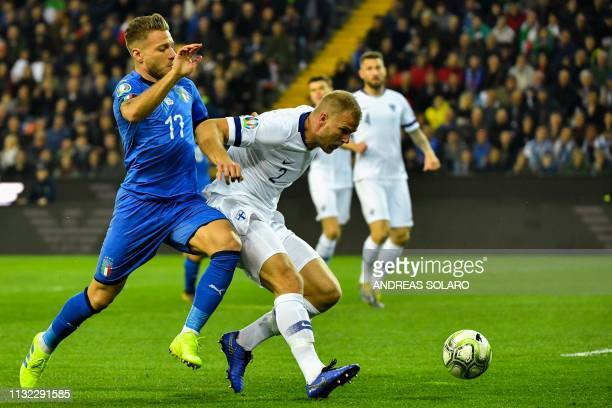 Finland's defender Paulus Arajuuri holds off Italy's forward Ciro Immobile during the Euro 2020 Group J qualifying football match between Italy and...