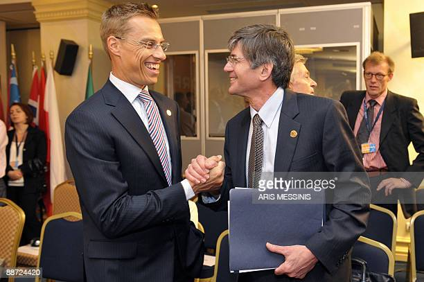 Finland's Foreign Minister Alexander Stubb shakes hands with US Deputy Secretary of State James Steinberg during an OSCE informal ministerial meeting...
