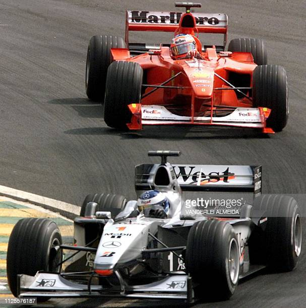 Finland's Formula One world champion Mika Hakkinen of Mclaren Mercedes disputes the turn with Brazilian Rubens Barrichello of Ferrari during the...