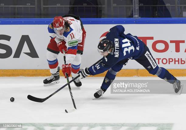 Finland's forward Julius Nattinen vies for the net with Russia's forward Dmitry Voronkov during the Channel One Cup of the Euro Hockey Tour ice...