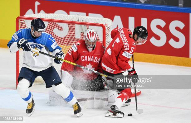Finland's forward Mikael Ruohomaa and Canada's defender Jacob Bernard-Docker vie for the puck in front of Canada's goalkeeper Darcy Kuemper during...