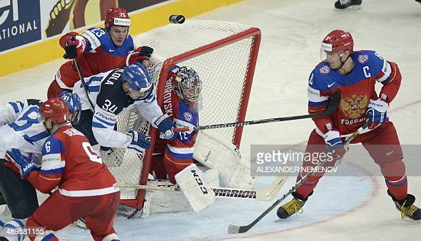 Finland's forward Olli Palola attacks Russia's goalie Sergei Bobrovski as Russia's forward Alexander Ovechkin looks at him during a preliminary round...