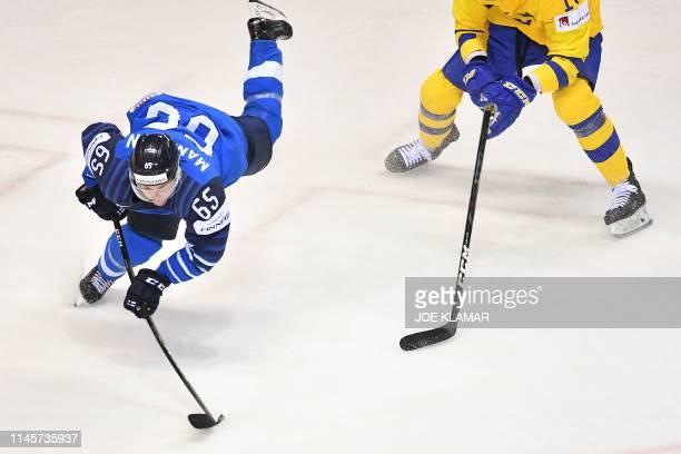 Finland's forward Sakari Manninen and Sweden's forward Alexander Wennberg vie for the puck during the IIHF Men's Ice Hockey World Championships...