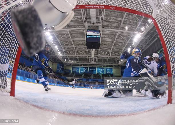 Finland's goalie Noora Raty looks on as a goal is scored by the US in the women's preliminary round ice hockey match between Finland and the US...