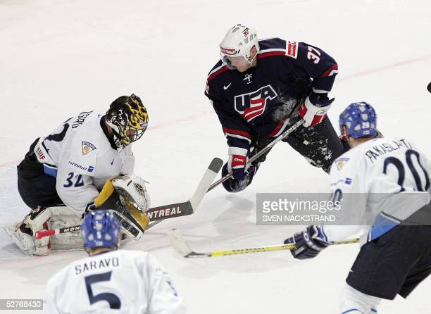 Finland's goaltender Niklas Backstrom saves an attack by US Mark Parrish during their ice hockey group match at the IIHF Mens World Championship in...