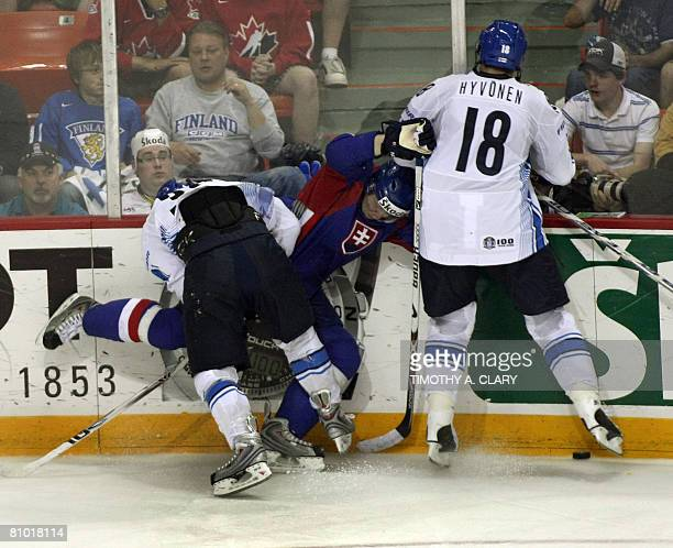 Finland's Hannes Hyvonen and Antii Pihlstrom smash Slovakia's Thomas Starosta into the boards during the preliminary round of the 2008 IIHF World...