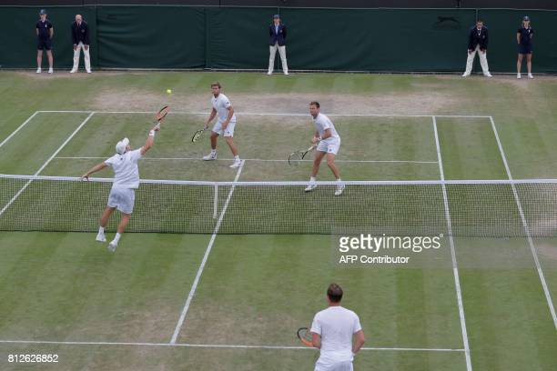 Finland's Henri Kontinen stands by as his partner Australia's John Peers volleys at the net against opponents US player Ryan Harrison and New...