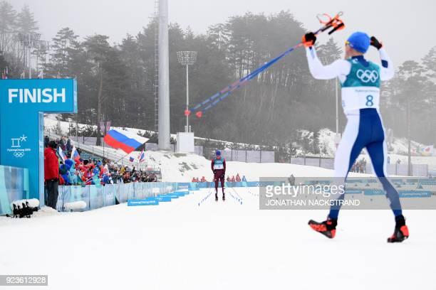 Finland's Iivo Niskanen celebrates winning gold as Russia's Alexander Bolshunov come in second in the men's 50km cross country mass start classic at...